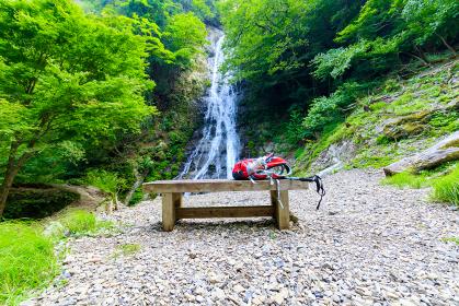木製のベンチの上に置かれたリュックサックと丸神の滝