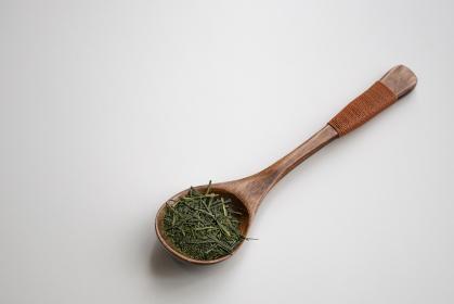木製のスプーンにのった緑茶の茶葉