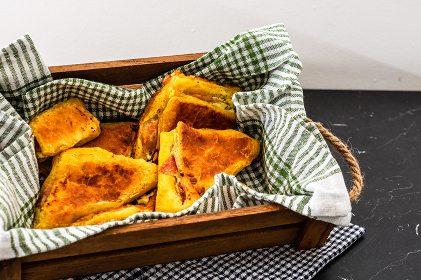 Freshly baked homemade ham and cheese puff pastry in a rustic crate.