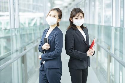 マスクをつけて立ち話するビジネスウーマン