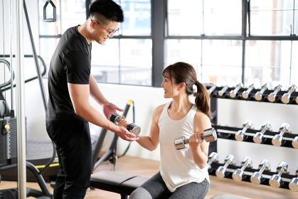 ダンベルトレーニングの指導をするアジア人男性トレーナー