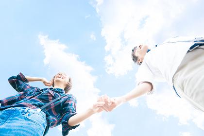 手をつなぐカップル(青空バック・白人・アジア人)