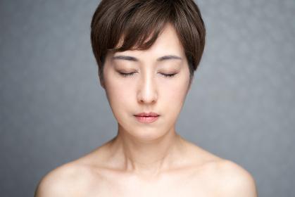 正面を向いて目をつぶる中年の日本人女性