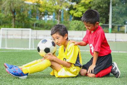 サッカーボールを持つ少年と友人