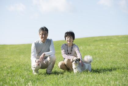 草原で微笑むシニア夫婦と犬