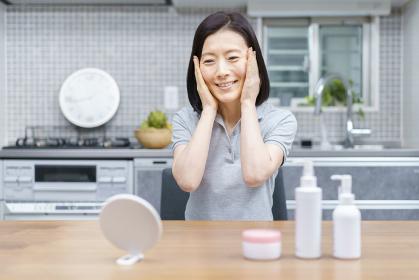 自宅で肌の状態を確かめる中年女性