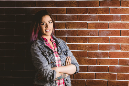 Smiling woman standing with arms crossed against brick wall