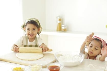 ピザ生地を伸ばす小さな双子の女の子