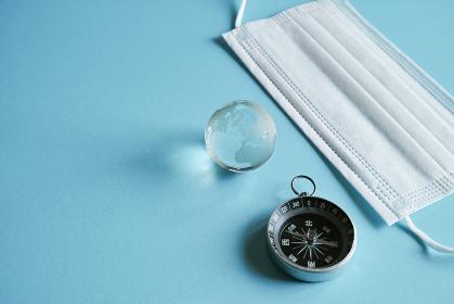 青い紙の上に置いた不織布マスクと方位磁石とガラスの地球とコピースペース