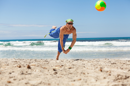adult young sporty man playing beach volleyball