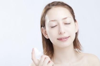 化粧水を吹きかける女性