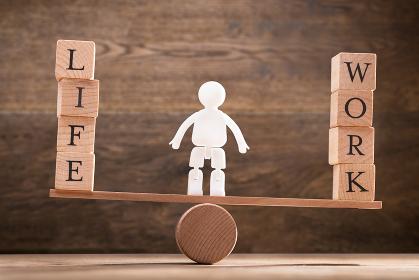 Human Figure Standing Between Work And Life Wooden Blocks