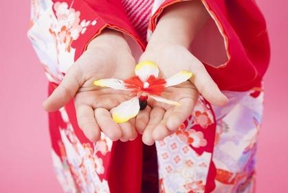 羽子板の羽根を持つ女児の手元