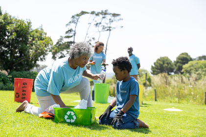 Side view of a senior African American woman and young boy kneeling in a field wearing gloves and t shirts with volunteer written on them, filling a green plastic recycling crate and talking, with a diverse group of volunteers collecting rubbish and recycling in the background