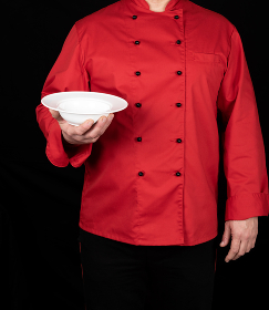 chef in red uniform holds in his right hand a round white plate for soup