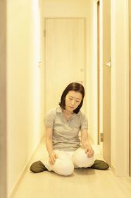 疲れて、廊下で座り込む中年女性