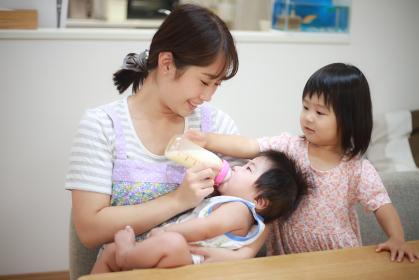 赤ちゃんにミルクを与える親子