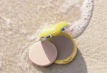 砂浜の波すれすれに置かれたUVフェースパウダー