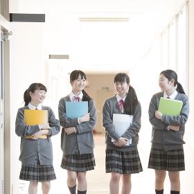 勉強道具を持ち廊下を歩く女子学生