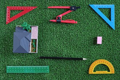 緑の人工芝に置いたミニチュアの家と定規などの文房具