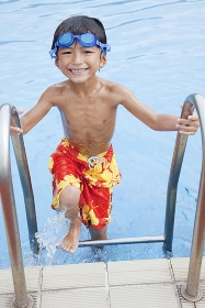 プールから上がる水着姿の男の子
