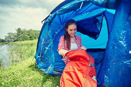 happy young woman sitting in tent at camping