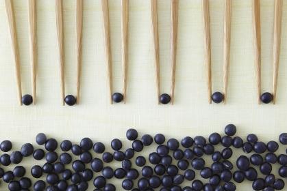 黒大豆を挟む6膳の箸と黒大豆