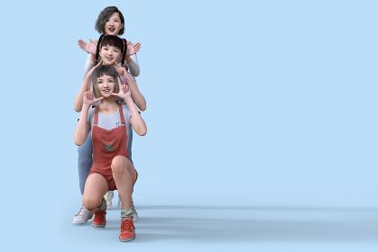 元気で仲のいい3人の女の子が楽しそうにトーテムポールのように縦に重なりかわいいポーズをとる