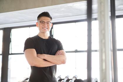 笑顔で腕組みをするアジア人男性トレーナー