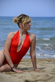 Rebel blonde girl poses sitted in swimsuit