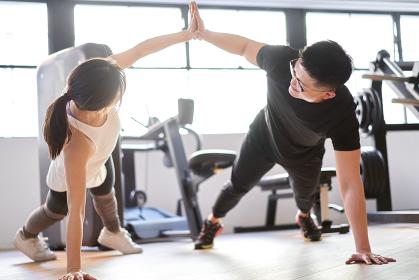 トレーニングジムでペアトレーニングをするアジア人カップル