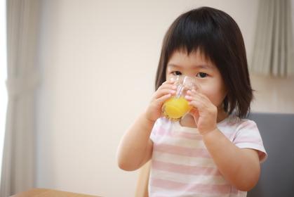 コップでジュースを飲む女の子