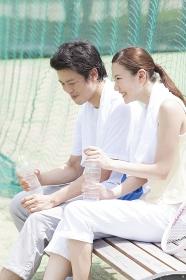 テニスコートのベンチに座って談笑する男女