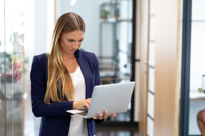Smartly dressed caucasian businesswoman standing in corridor using laptop computer. business in a modern office.