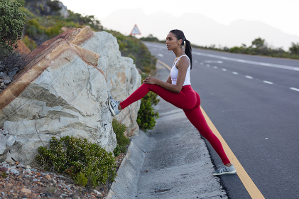 Fit african american woman in sportswear stretching on a coastal road. healthy lifestyle, exercising in nature.