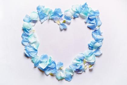 造花の青い花と花びらで模ったハートのフレーム。白いコピースペース。平置きの俯瞰撮影。白バック。