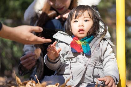 落ち葉と子供(秋のイメージ)