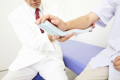 腕の骨折をシーネで固定する医者