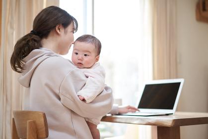 赤ちゃんの子守りをしながら仕事をするアジア人のお母さん
