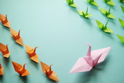 ピンク色の大きな折り鶴が向く空間を挟んで、橙色と黄緑色の小さい複数の折り鶴が対峙している。