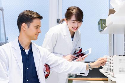 実験室で研究開発・解析・調査をする白衣の男性と女性