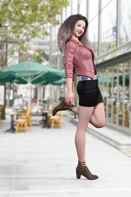 ワッフルヘアをした女性がピンクベージュのライダースジャケットを羽織り片足を後ろに曲げて両手を添える