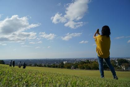 眺めの良い公園で青空のもと芝生の上で4人の友達をスマホで撮る1人の女性