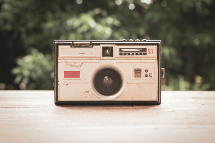 Old photo camera from the 60s on rustic wooden tab