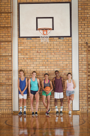 High school kids leaning against the wall in basketball court