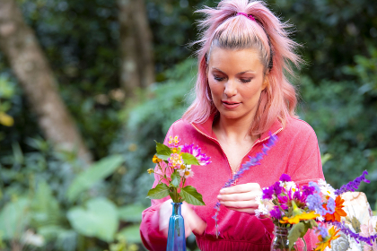 A beautiful 34 year old blond woman arranging cut flowers from her garden.