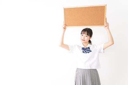 コルクボードを持つ学生
