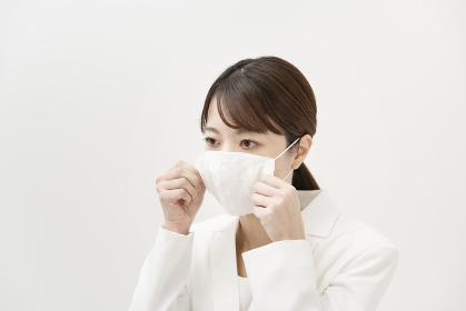 マスクを着ける白いスーツ姿の女性