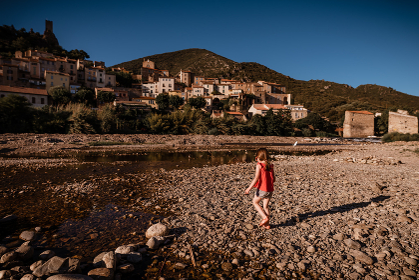 Girl walks across rocky river beach in south of France