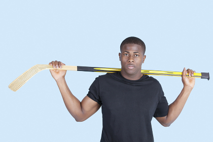 Portrait of an African American man holding hockey stick over blue background